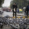 An Indian man feeds pigeons on a rainy morning in New Delhi, India, Tuesday, Feb. 5, 2013. Heavy rains accompanied by thunderstorm lashed the capital for the second day Tuesday throwing traffic out of gear across the city. (AP Photo/Altaf Qadri)