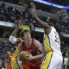 Photo - Houston Rockets' Omer Asik (3) puts up a shot against Indiana Pacers' Roy Hibbert, right, during the first half of an NBA basketball game Friday, Jan. 18, 2013, in Indianapolis. (AP Photo/Darron Cummings)