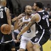San Antonio Spurs\' Tony Parker, center, of France, is defended by Brooklyn Nets\' Deron Williams during the first half of an NBA basketball game, Monday, Dec. 31, 2012, in San Antonio. (AP Photo/Darren Abate)