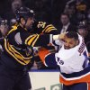 Buffalo Sabres left winger John Scott (32) lands a punch to the side of the head on New York Islanders right winger Justin Johnson (49) during the first period of an NHL hockey game in Buffalo, N.Y., Sunday April 13, 2014. (AP Photo/Gary Wiepert)