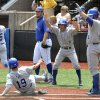 Photo - Kentucky's Matt Reida, center, celebrates as teammate Austin Cousino (19) slides in to score during the fourth inning of an NCAA college baseball regional tournament game in Louisville, Ky., Sunday, June 1, 2014. (AP Photo/Timothy D. Easley)