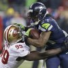 Photo - Seattle Seahawks' Marshawn Lynch tries to run past San Francisco 49ers' Aldon Smith during the second half of the NFL football NFC Championship game Sunday, Jan. 19, 2014, in Seattle. (AP Photo/Elaine Thompson)
