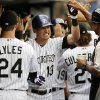 Photo - Colorado Rockies' Drew Stubbs (13) is congratulated by teammates in the dugout after hitting a two run home run off Minnesota Twins starting pitcher Kris Johnson during the first inning of a baseball game on Friday, July 11, 2014, in Denver. (AP Photo/Jack Dempsey)