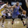 Photo - Oklahoma City Thunder guard Russell Westbrook, right, drives on Indiana Pacers guard George Hill in the first half of an NBA basketball game in Indianapolis, Friday, April 6, 2012. (AP Photo/Michael Conroy) ORG XMIT: NAF105
