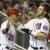 Photo - Washington Nationals Ian Desmond, left, congratulates Bryce Harper after Harper scored during the third inning of a baseball game against the Arizona Diamondbacks on Tuesday, Aug. 19, 2014, in Washington. (AP Photo/Evan Vucci)