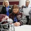 Jordan Weltzheimer signs to play football with Air Force as his parents, Marie Weltzheimer and Ron Weltzheimer, watch during the college signing day ceremony for student athletes at Edmond Memorial High School in Edmond, Okla., Wednesday, Feb. 5, 2014. Photo by Nate Billings, The Oklahoman