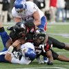 Photo -   Kansas quarterback Kayne Crist is sacked for a 6-yard loss by Northern Illinois defensive end Joe Windsor, right, as defensive end Alan Baxter assists on the play during the fourth quarter of an NCAA college football game in DeKalb, Ill., on Saturday, Sept. 22, 2012. Northern Illinois defeated Kansas 30-23. (AP Photo/Daily Chronicle, Rob Winner) CHICAGO LOCALS OUT ROCKFORD OUT
