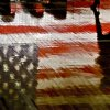The American flag reflects on the gym floor as a student walks by during Yukon High School\'s Veterans Day Celebration on Monday Nov. 12 2012, in Yukon, Oklahoma. Photo by Chris Landsberger, The Oklahoman