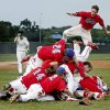 The Silo baseball team including B.W. Savage, upper right, celebrates as Oktaha\'s Derrick Skinner walks off the field following Silo\'s win in the Class 2A state baseball championship in Oklahoma City, Saturday, May 15, 2010. Photo by Bryan Terry, The Oklahoman
