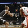 Photo - Brooklyn Nets' Alan Anderson, left, defends against Miami Heat's LeBron James, right, during the first half of an NBA basketball game on Friday, Jan. 10, 2014, in New York. Both teams wore nicknames on their jerseys during the game. (AP Photo/Frank Franklin II)