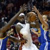 Miami Heat\'s LeBron James, center, is defended by Golden State Warriors\' Draymond Green (23) and Stephen Curry (30) during an NBA basketball game on Wednesday, Dec. 12, 2012, in Miami. (AP Photo/Rhona Wise)