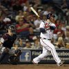 Photo - Atlanta Braves' Brian McCann (16) follows through with a solo home run as Minnesota Twins catcher Joe Mauer (7) watches in the fourth inning of a baseball game Tuesday, May 21, 2013 in Atlanta. (AP Photo/John Bazemore)