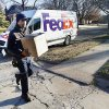 Photo - FedEx courier Kendall Ellis delivers packages Monday in northwest Oklahoma City. FedEx expected to set a record for number of packages delivered Monday.