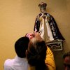 **For People on Sunday Photo Column** Antonio Aguirre fulfills a promise as he and his family visit the National Shrine Infant Jesus of Prague at St. Wenceslaus Catholic Church in Prague, Oklahoma on Sunday, August 2, 2009. By John Clanton, The Oklahoman ORG XMIT: KOD