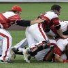 Photo - CORRECTS TO 2013-Louisville players pile on top of pitcher Cody Edge, bottom, after getting the final out in the ninth inning of an NCAA college baseball tournament super regional game on Sunday, June 9, 2013, in Nashville, Tenn. Louisville won 2-1 to advance to the College World Series. (AP Photo/Mark Humphrey)