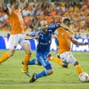 Photo - Montreal Impact midfielder Justin Mapp, center, is taken down by Houston Dynamo midfielder Corey Ashe, right, as he gets past midfielder Brad Davis during the first half of an MLS soccer game Friday, Oct. 4, 2013, in Houston. (AP Photo/Houston Chronicle, Smiley N. Pool) MANDATORY CREDIT