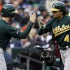 Oakland Athletics\' Coco Crisp is congratulated after hitting a solo home run during the first inning of Game 1 of the American League division baseball series against the Detroit Tigers, Saturday, Oct. 6, 2012, in Detroit. (AP Photo/Paul Sancya)