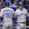 Photo - Toronto Blue Jays' Jose Bautista (19) is congratulated by teammate Brett Lawrie after scoring on Dioner Navarro's sacrifice fly during the fourth inning of a baseball game against the Tampa Bay Rays in St. Petersburg, Fla., Thursday, April 3, 2014. (AP Photo/Phelan M. Ebenhack)