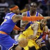 Photo - Cleveland Cavaliers' Wayne Ellington, right, passes the ball under pressure from New York Knicks' Carmelo Anthony, left, and Amare Stoudemire during the first quarter of an NBA basketball game, Monday, March 4, 2013, in Cleveland. (AP Photo/Tony Dejak)