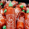 Photo - Sriracha chili sauce bottles are produced at the Huy Fong Foods factory in Irwindale, Calif., on Tuesday, Oct 29, 2013. The maker of Sriracha hot sauce is under fire for allegedly fouling the air around its Southern California production site. The city of Irwindale filed a lawsuit in Los Angeles Superior Court Monday asking a judge to stop production at the Huy Fong Foods factory, claiming the chili odor emanating from the facility is a public nuisance. (AP Photo/Nick Ut)