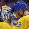 Photo - Sweden defenseman Alexander Edler congratulates goaltender Henrik Lundqvist on a shutout against Slovenia at the end of a men's quarterfinal ice hockey game at the 2014 Winter Olympics, Wednesday, Feb. 19, 2014, in Sochi, Russia. (AP Photo/Julio Cortez)