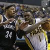 Photo - Indiana Pacers' Lance Stephenson (1) goes to the basket against Brooklyn Nets' Paul Pierce (34) during the second half of an NBA basketball game Saturday, Dec. 28, 2013, in Indianapolis. Indiana defeated Brooklyn 105-91. (AP Photo/Darron Cummings)