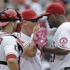 Los Angeles Angels pitching coach Mike Butcher, center, talks to starting pitcher Jerome Williams, as catcher Chris Iannetta listens during the fifth inning of a baseball game against the Oakland Athletics in Anaheim, Calif., Sunday, July 21, 2013. (AP Photo/Reed Saxon)