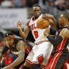 Photo - Chicago Bulls forward Luol Deng, center, tries to control the ball against Miami Heat forward LeBron James, left, and guard Mario Chalmers, right, during the first half of an NBA basketball game in Chicago, Thursday, Dec. 5, 2013. (AP Photo/Kamil Krzaczynski)