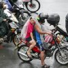 Motorists shield themselves during a slight rain brought about by typhoon Melor (local name