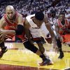 Photo - Chicago Bulls forward Taj Gibson, left, and Miami Heat guard Norris Cole battle for a loose ball as guard Nate Robinson, far right, watches during the first half of Game 2 of their NBA basketball playoff series in the Eastern Conference semifinals, Wednesday, May 8, 2013, in Miami. (AP Photo/Lynne Sladky)