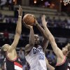 Photo - Charlotte Bobcats' Al Jefferson, middle, aims his short jumper through the defense of Portland Trail Blazers' Nicolas Batum, left, and Robin Lopez, right, during the first half of an NBA basketball game in Charlotte, N.C., Saturday, March 22, 2014. (AP Photo/Bob Leverone)