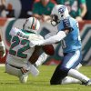 Miami Dolphins running back Reggie Bush (22) fumbles the ball as he is tackled by Tennessee Titans cornerback Jason McCourty, right, during the first half of an NFL football game, Sunday, Nov. 11, 2012, in Miami, Fla. (AP Photo/John Bazemore)