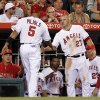 Photo - Los Angeles Angels' Mike Trout (27) and the bench congratulates Albert Pujols (5), who scored on a single by Eric Aybar in the sixth inning of a baseball game against the Cleveland Indians on Tuesday, April 29, 2014, in Anaheim, Calif. (AP Photo/Alex Gallardo)