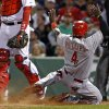 Photo - Cincinnati Reds' Brandon Phillips (4) slides into home to score on Ryan Ludwick's sacrifice fly as Boston Red Sox catcher A.J. Pierzynski (40) stands by during the eighth inning of a baseball game at Fenway Park in Boston, Tuesday, May 6, 2014. (AP Photo/Elise Amendola)