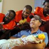 From upper left, Oklahoma State\'s Nick Rockwell, Tracy Moore and Nigel Nicholas pose for a photo with Juston Marshall and his 9-week-old daughter, Libbye Marshall during a visit by OSU football players to The Children\'s Hospital in Oklahoma City, Wednesday, July 11, 2012. Libbye Marshall is a patient at The Children\'s Hospital. Photo by Nate Billings, The Oklahoman