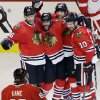 Chicago Blackhawks\' Johnny Oduya (27), second from left, celebrates with Michal Handzus (26), Michal Rozsival (32), Patrick Sharp (10) and Patrick Kane (88) after scoring his goal during the third period of Game 1 of an NHL hockey playoffs Western Conference semifinal against the Detroit Red Wings in Chicago, Wednesday, May 15, 2013. (AP Photo/Nam Y. Huh)