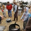 Justin Lewis, 8, of Meeker extends his hands over an open fire as he and others gather near the fire pit, hoping to get some relief from the cold. The fire was part of a cooking demonstration by workers at Big Pasture Ranch in El Reno. The chuck wagon crew were making from-scratch biscuits and hot coffee for guests. Children with their parents endured cold temperatures and intermittent rain to come to the grounds of the Oklahoma History Center on Saturday, March 23, 2013, to participate in the 3rd annual Cowboy Round-up, billed to be a