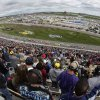 Photo - Fans cheer as drivers resume racing after a caution during a NASCAR Sprint Cup series auto race at Kansas Speedway in Kansas City, Kan., Sunday, Oct. 6, 2013. (AP Photo/Charlie Riedel)
