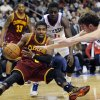 Cleveland Cavaliers\' Kyrie Irving (2) turns the ball over as he falls in front of Philadelphia 76ers\' Spencer Hawes (00) and Jrue Holiday (11) during the second half of an NBA basketball game on Sunday, Nov. 18, 2012, in Philadelphia. The 76ers won 86-79. (AP Photo/Michael Perez)