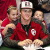 Justice Hansen, center, is an Edmond Santa Fe quarterback who signed a letter of intent to play football with OU during signing day ceremony in the gymnasium at Edmond Santa Fe High School on Wednesday, Feb. 5, 2014. Siblings Kasia, 8, left, and Acyn, 6, were beside Hansen when he signed the ceremonial letter. Photo by Jim Beckel, The Oklahoman