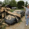 A compact car is uncovered in the street on Saturday, April 14, 2012, in Norman, Okla. This resident of Nancy Linn Terrace (who did not want his name published) says strangers showed up right after Friday\'s tornado to help cut limbs from the giant tree that blew down and hit his brother\'s car. Photo by Steve Sisney, The Oklahoman