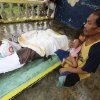A resident cuddles his child next to the bodies of three children who were killed in a landslide that swept their home after Typhoon Bopha made a landfall in Compostela Valley in southeastern Philippines Tuesday, Dec. 4, 2012. Typhoon Bopha , one of the strongest typhoons to hit the Philippines this year, barreled across the country\'s south on Tuesday, killing dozens of people and forcing more than 50,000 to flee from inundated villages. (AP Photo/Karlos Manlupig)