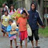 Residents evacuate to safer grounds in anticipation of Typhoon Bopha in Butuan city in southeastern Philippines Tuesday, Dec. 4, 2012. Typhoon Bopha, one of the strongest typhoons to hit the Philippines this year, barreled across the country\'s south on Tuesday, killing dozens of people and forcing more than 50,000 to flee from inundated villages. (AP Photo/Erwin Mascarinas)