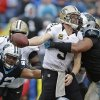 Photo - New Orleans Saints' Drew Brees, center, tries to pass as he is hit by Carolina Panthers' Greg Hardy, right, and Dwan Edwards, left, in the second half of an NFL football game in Charlotte, N.C., Sunday, Dec. 22, 2013. The Panthers won 17-13. (AP Photo/Bob Leverone)