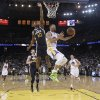 Photo - Golden State Warriors guard Stephen Curry, center left, drives to the basket as Utah Jazz guard Alec Burks (10) defends during the first half of an NBA basketball game Sunday, April 6, 2014, in Oakland, Calif. (AP Photo/Marcio Jose Sanchez)