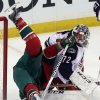 Photo - Minnesota Wild's Matt Cooke, left, topples over Columbus Blue Jackets goalie Sergei Bobrovsky, of Russia, in the first period of an NHL hockey game, Saturday, March 15, 2014, in St. Paul, Minn. (AP Photo/Jim Mone)