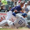 Photo - Los Angeles Dodgers' Josh Beckett (61) slides safely into third base while advancing on a single by Dee Gordan as Colorado Rockies third baseman Nolan Arenado, top, fields the throw in the fifth inning of a baseball game in Denver, Sunday, July 6, 2014. (AP Photo/David Zalubowski)