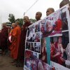 Buddhist monks hold prayers with photos of monks injured in crackdown at the Letpadaung copper mine in Monywa, northwestern Myanmar, in Yangon, Myanmar, Friday, Nov. 30, 2012. Opposition leader Aung San Suu Kyi publicly criticized the forcible crackdown on protesters at the mine and said Friday that the public needed an explanation of the violence that injured dozens, including Buddhist monks. (AP Photo/Khin Maung Win)