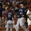 Photo - Seattle Mariners' Dustin Ackley (13) and James Paxton (65) celebrate after scoring on a two-run double by Franklin Gutierrez as St. Louis Cardinals catcher Yadier Molina, right, stands by during the fifth inning of a baseball game, Saturday, Sept. 14, 2013, in St. Louis. (AP Photo/Jeff Roberson)