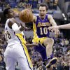 Los Angeles Lakers guard Steve Nash, right, loose the ball as he attempts a shot over Indiana Pacers center Ian Mahinmi in the first half of an NBA basketball game in Indianapolis, Friday, March 15, 2013. (AP Photo/Michael Conroy)